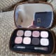 Along with the eight eye shadows, the case contains a high quality full-sized mirror and a double-ended brush with one dense, full side for packing on color and one narrower side for lining and smoking shades out.