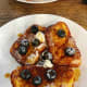 Homemade French toast served with butter, fresh blueberries, and maple syrup