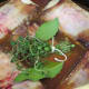 Short ribs, water, bay leaves, and thyme added to the pot and ready to cover and bake in the oven.
