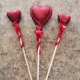 Add pizazz to your decorative hearts by wrapping a red pipe cleaner around the sticks.