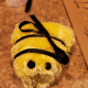 Wrap a black ribbon around the bee, tying a bow at the top to create stripes.