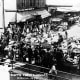 Vegetable vendors and horse-drawn wagons at the Pike Place Market, probably between 1907 and 1920