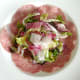 Salad is arranged on top of salami bed
