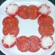 Chorizo slices are arranged around plate border