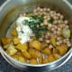 Combining potato and chickpea salad ingredients