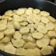 Arrange the sliced potatoes in a baking dish.