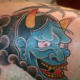 A blue hannya mask tattoo.