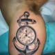 Pocket watch tattoo with an anchor.