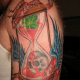 An hourglass tattoo with blood, skull, wings, and four-leaf clover.