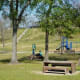 View of picnic tables, playground, and hill