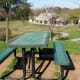 One of two picnic tables on top of a hill in the park overlooking the pavilion, sports field, and parking lot