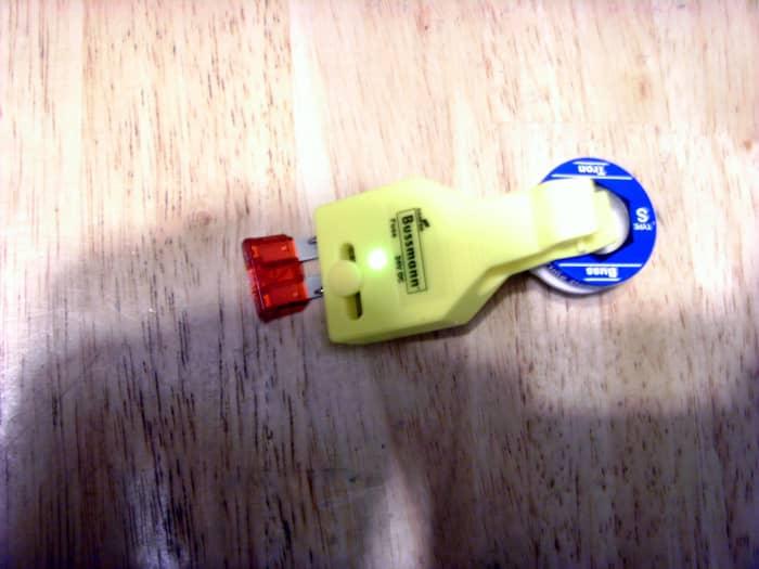 Testare un fusibile a lama ATC automobilistico. La luce al centro del tester è accesa, indicando un buon fusibile.