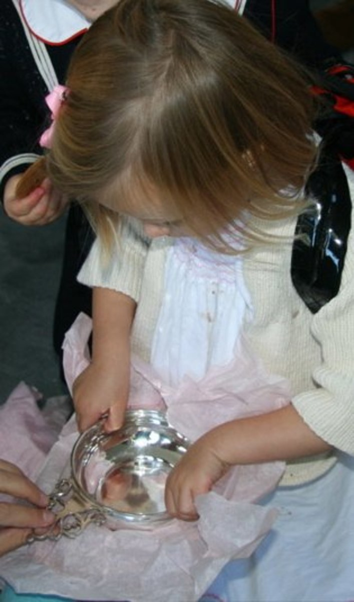 A girl opens a Christening present containing a porringer.