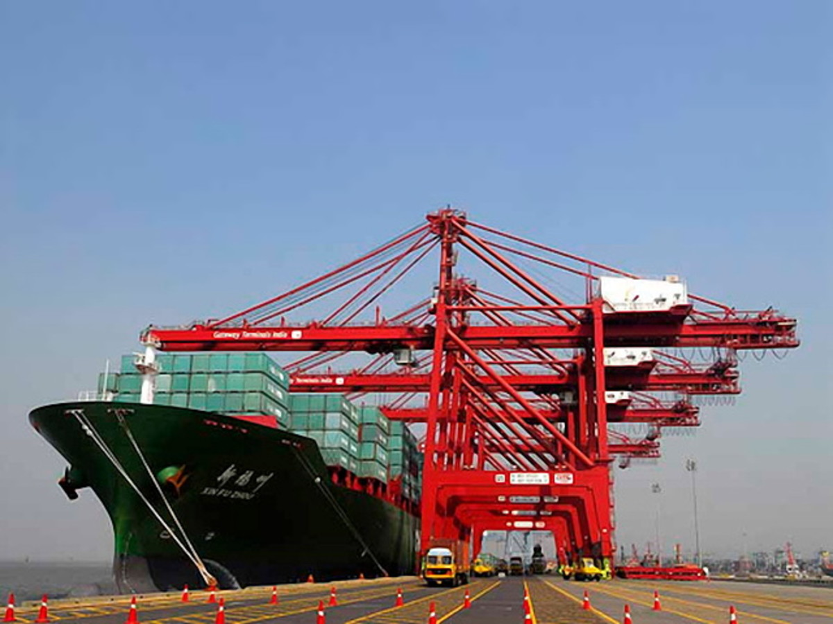 Merchant ship being unloaded at Jawaharlal Nehru Trust Port in Navi Mumbai, India (CC BY 3.0).