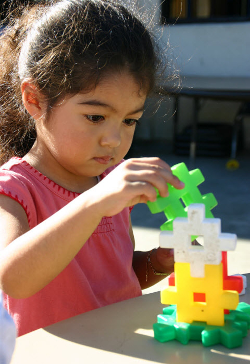 She is actively absorbed figuring out how and where to place the piece.