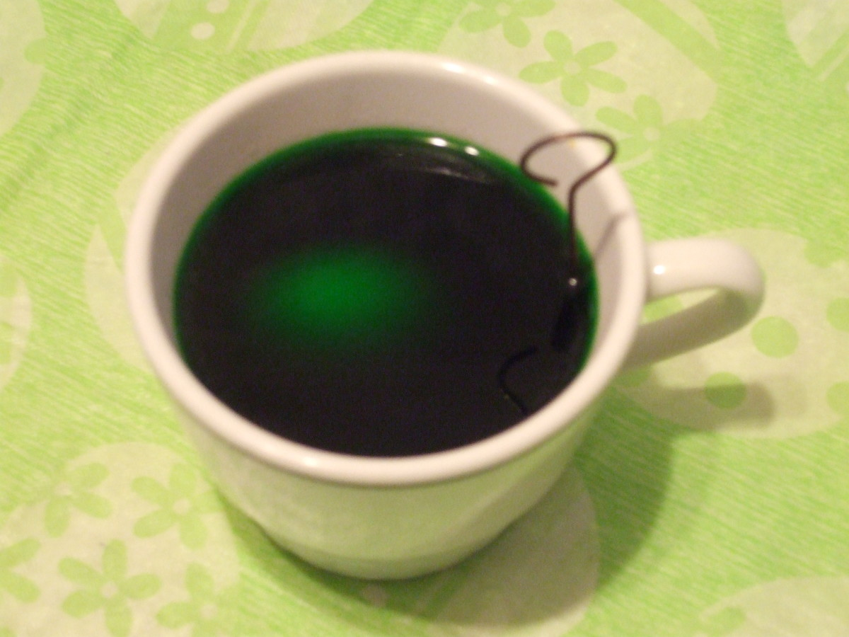Dyeing a hard-boiled egg in a teacup. Green eggs, but no ham here!