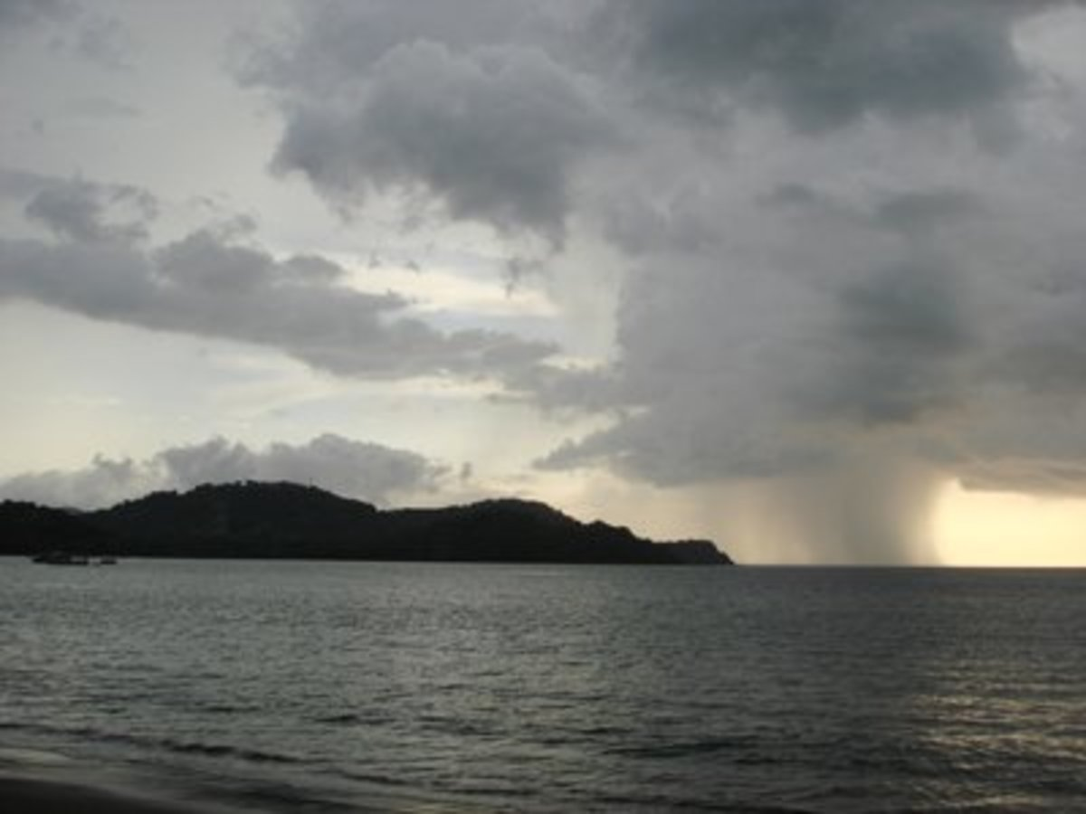 Partly cloudy with scattered rain showers in the afternoon is common during the wet season. A view westward from Playa Panama into Bahia Culebra.