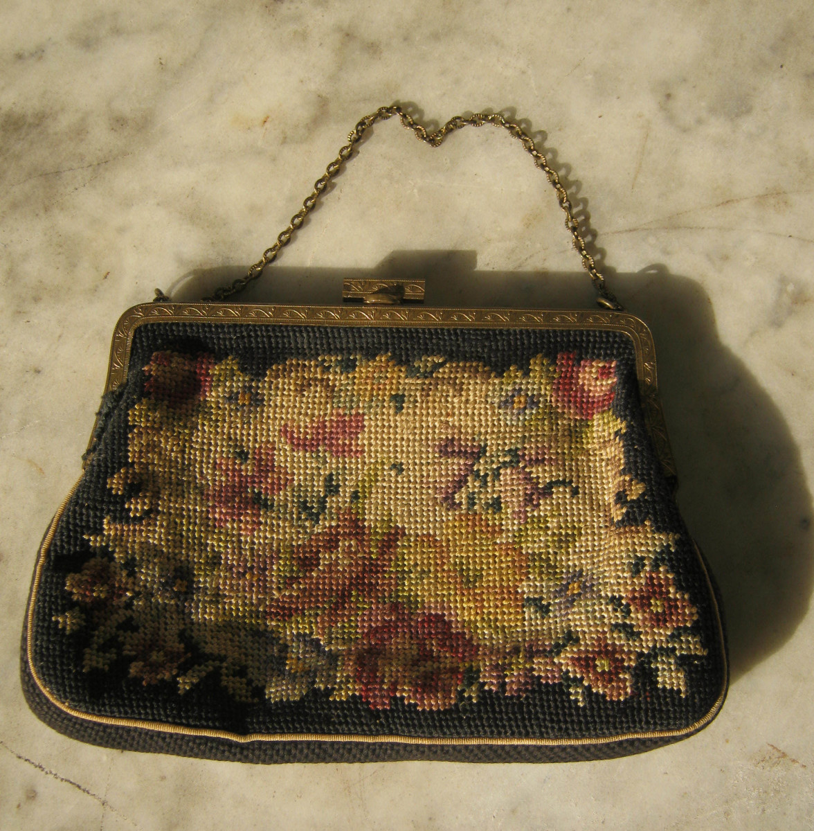 Tapestry bag with metal frame and chain handle.
