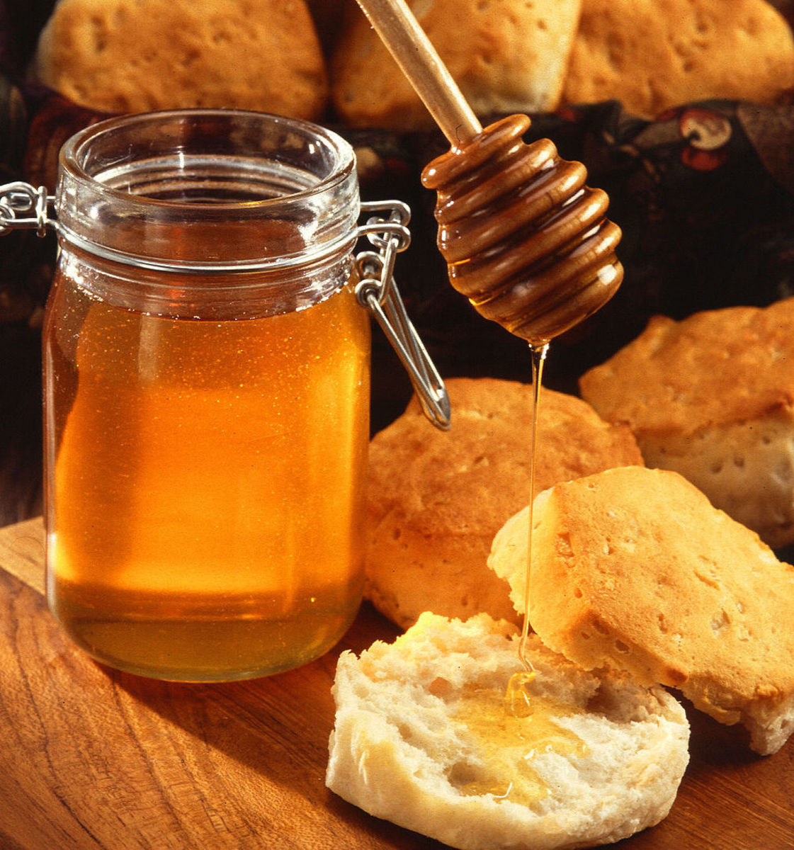 A jar of honey with a honey dipper and an American biscuit.