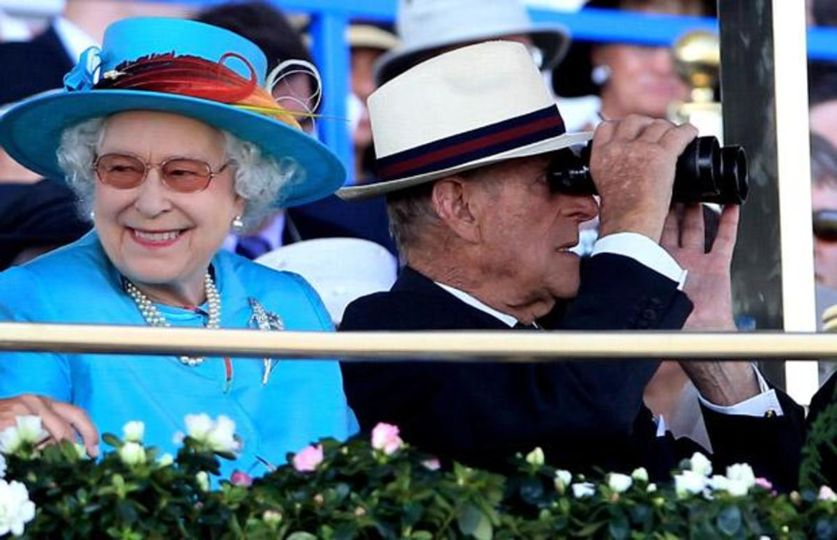 The Queen smiles during a day at the races while the Duke of Edinburgh uses binoculars to watch the field  of horses