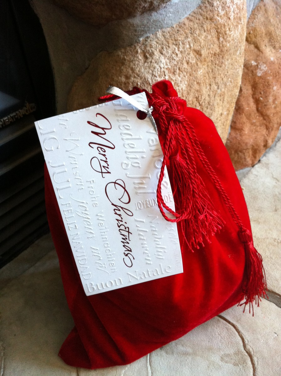 Christmas gift wrapped in a reusable velvet bag with gift tag made from a recycled Christmas card.
