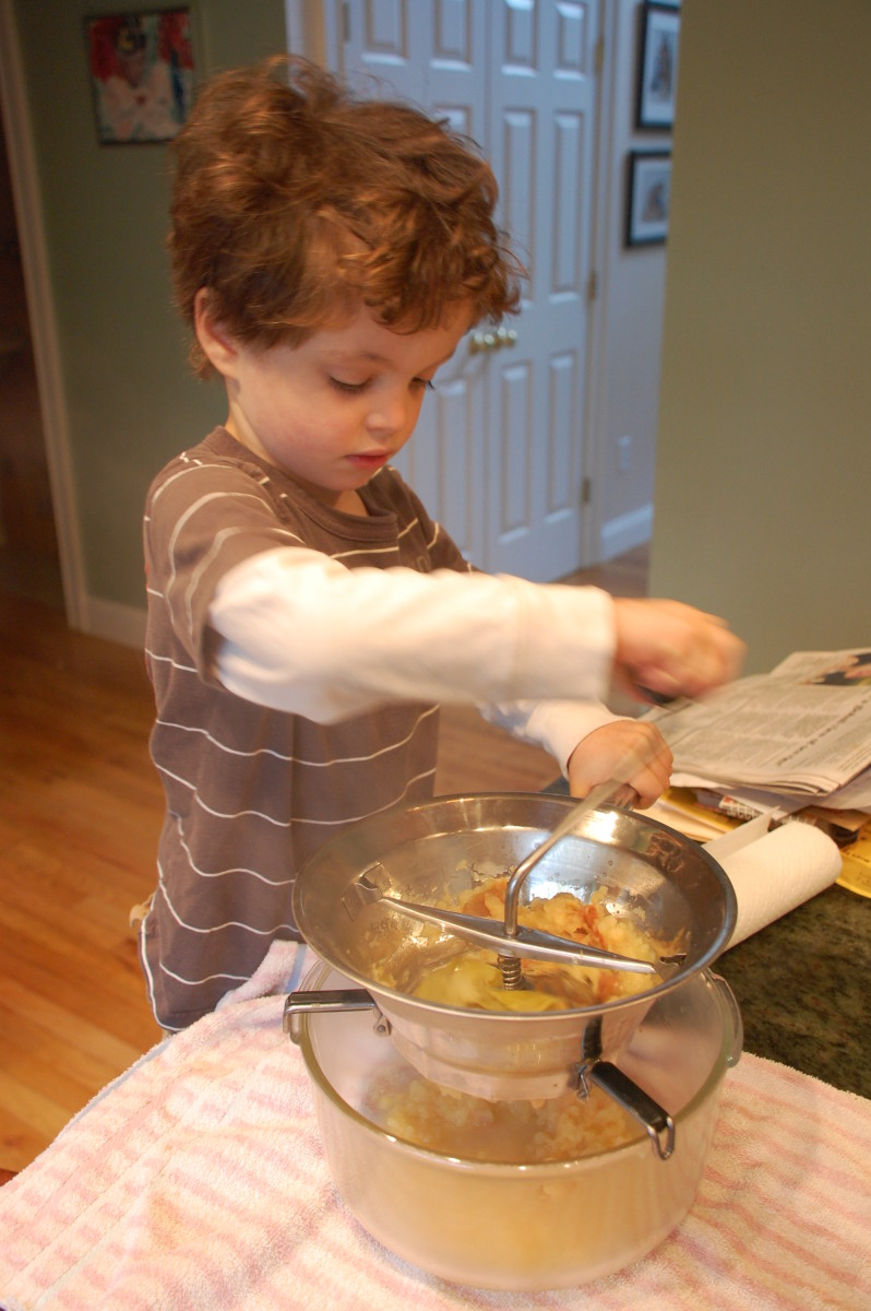 Here a Waldorf student is straining apples to make applesauce.