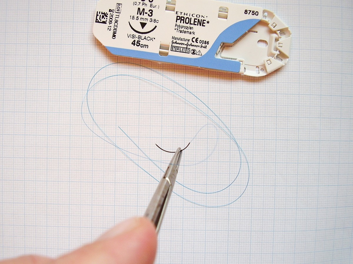 An atraumatic (swaged) needle and attached thread held in a needle holder; in this case, the suturing needle is curved