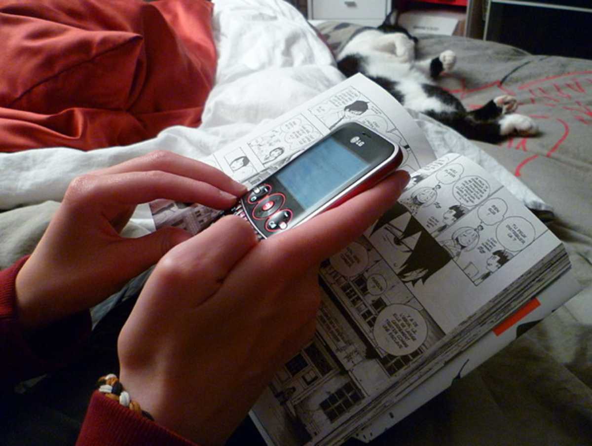Texting while reading a manga comicbook.