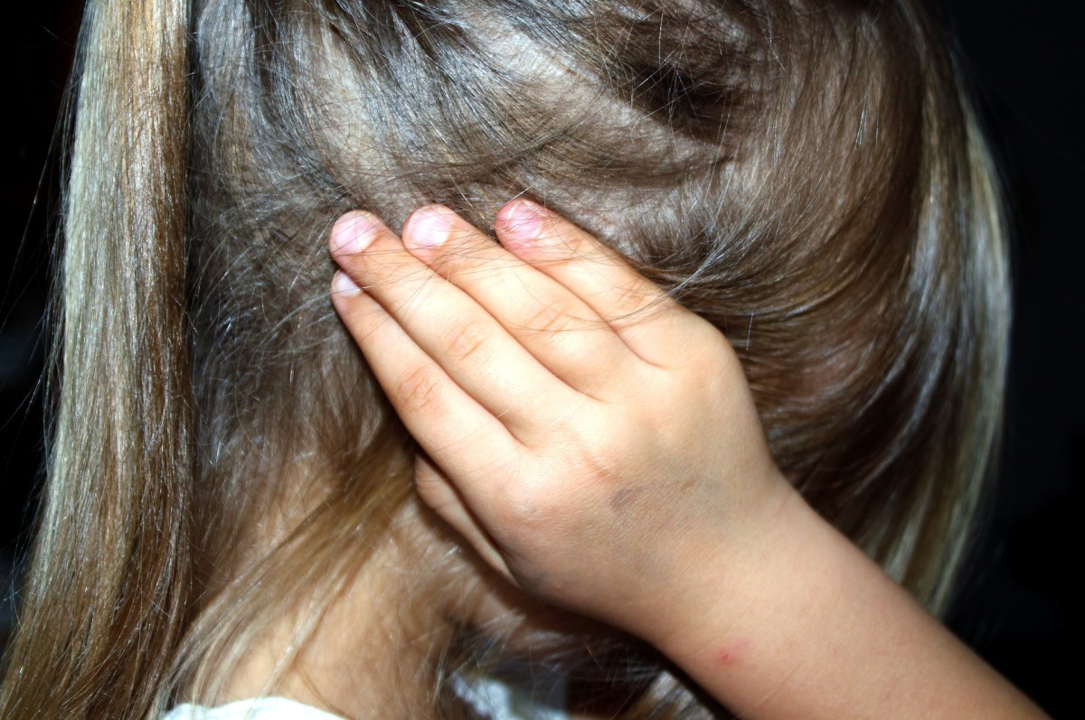 A child covering her ears due to noisy surroundings.