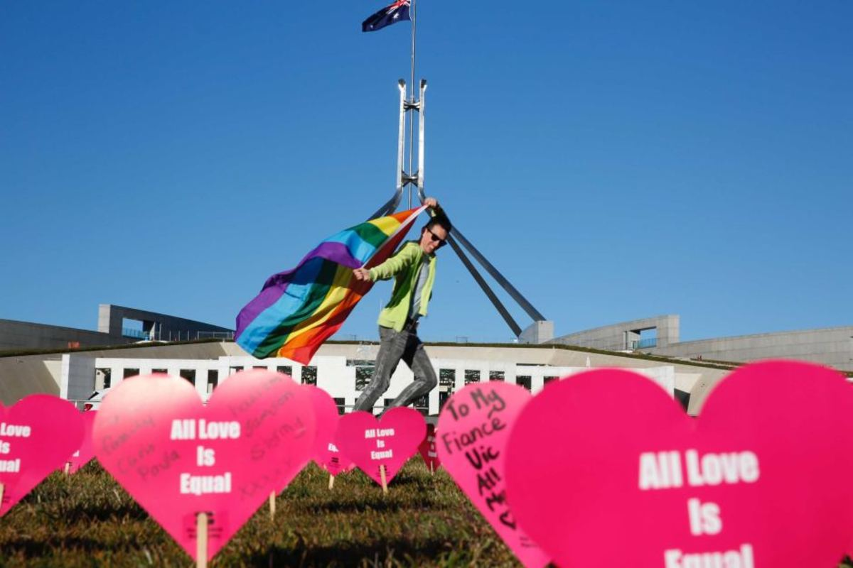 Protester carries rainbow flag in front of Parliament House (8 Aug 2017)