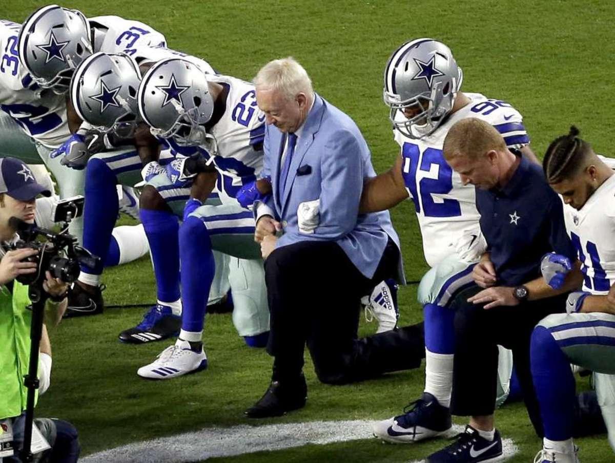 Dallas Cowboys kneel with owner Jerry Jones.
