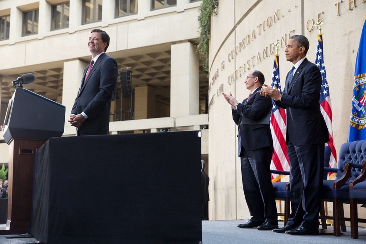 Then-FBI Director James Comey receives applause from former President Barack Obama and former FBI Deputy Director Sean Joyce during installation proceedings in Washington, D.C., in 2013.