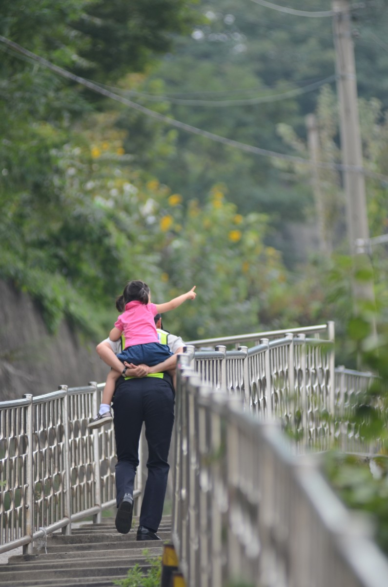 Officer helping child across a bridge.