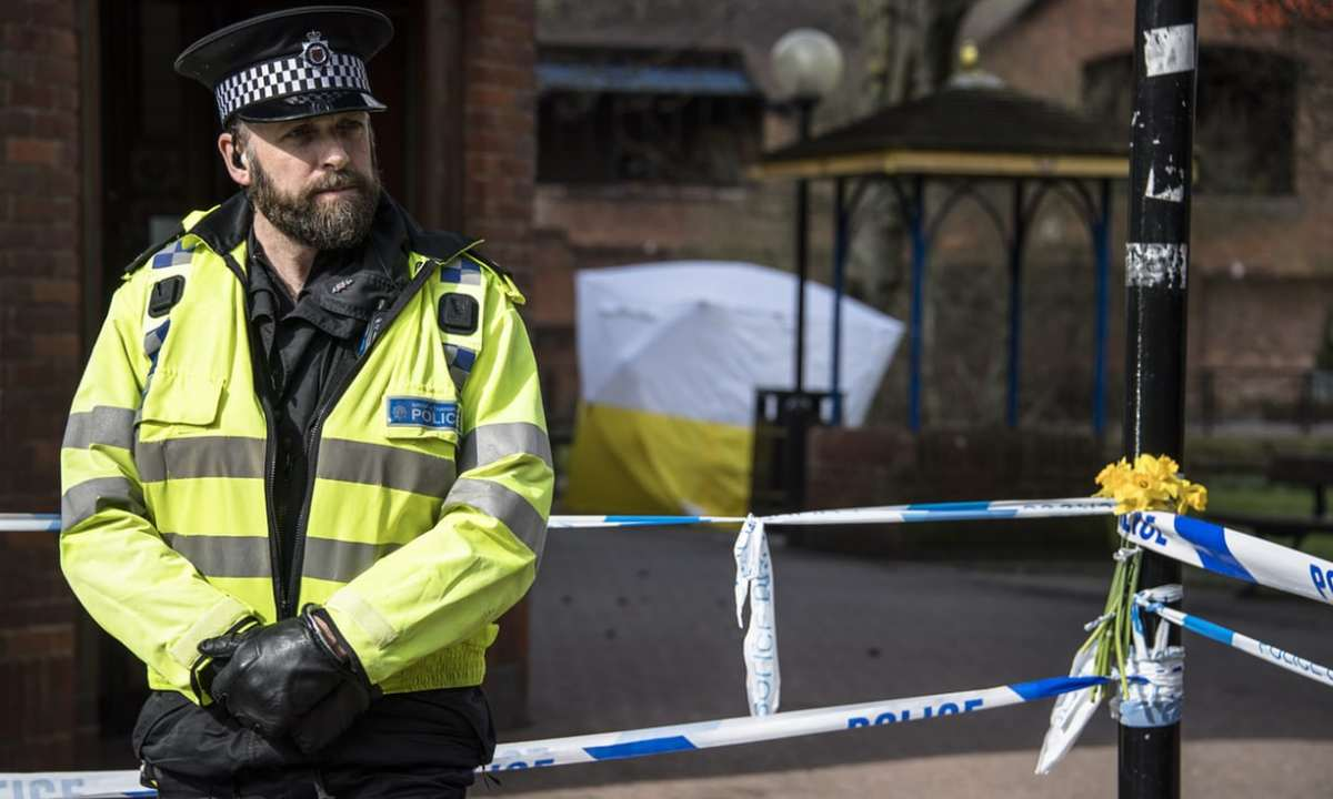 A British police officer stands before the cordoned off area in Salisbury