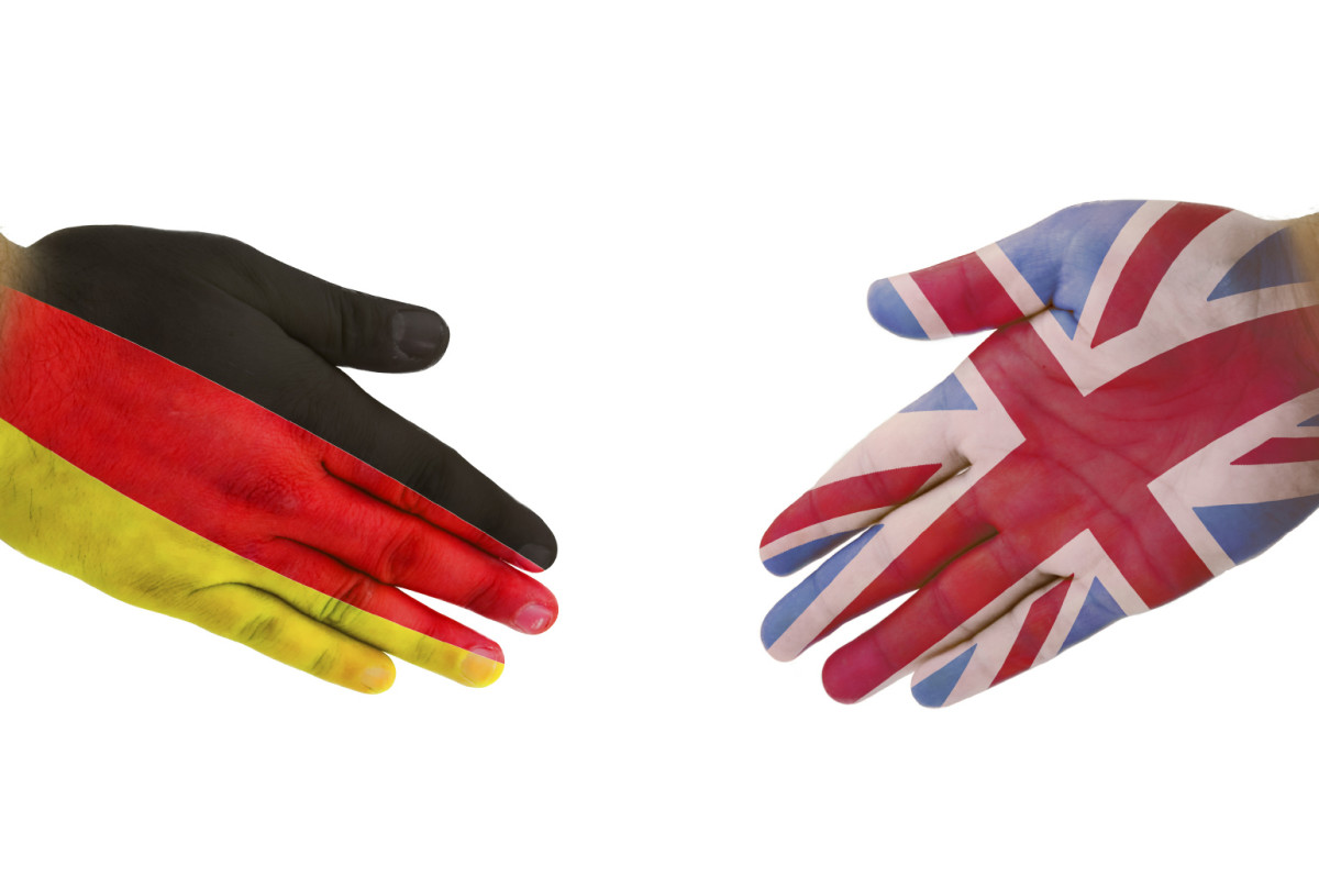 Two hands, one coloured in the Germany flag and the other with the UK flag