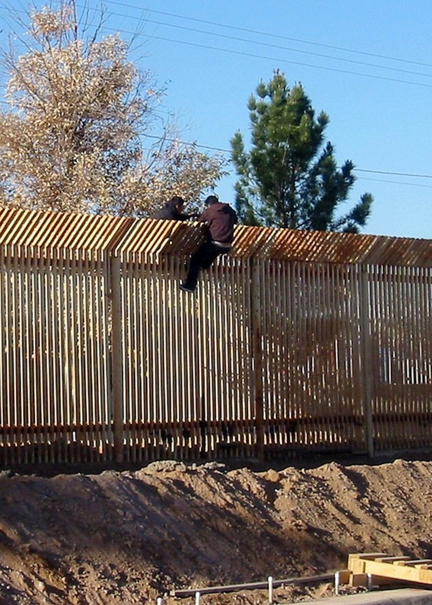 Two men climb over the current Mexico/U.S. border barrier.