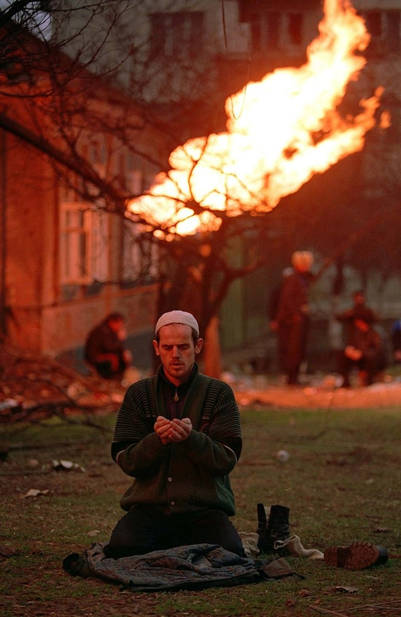 Chechen man prays during conflict in Grozny.