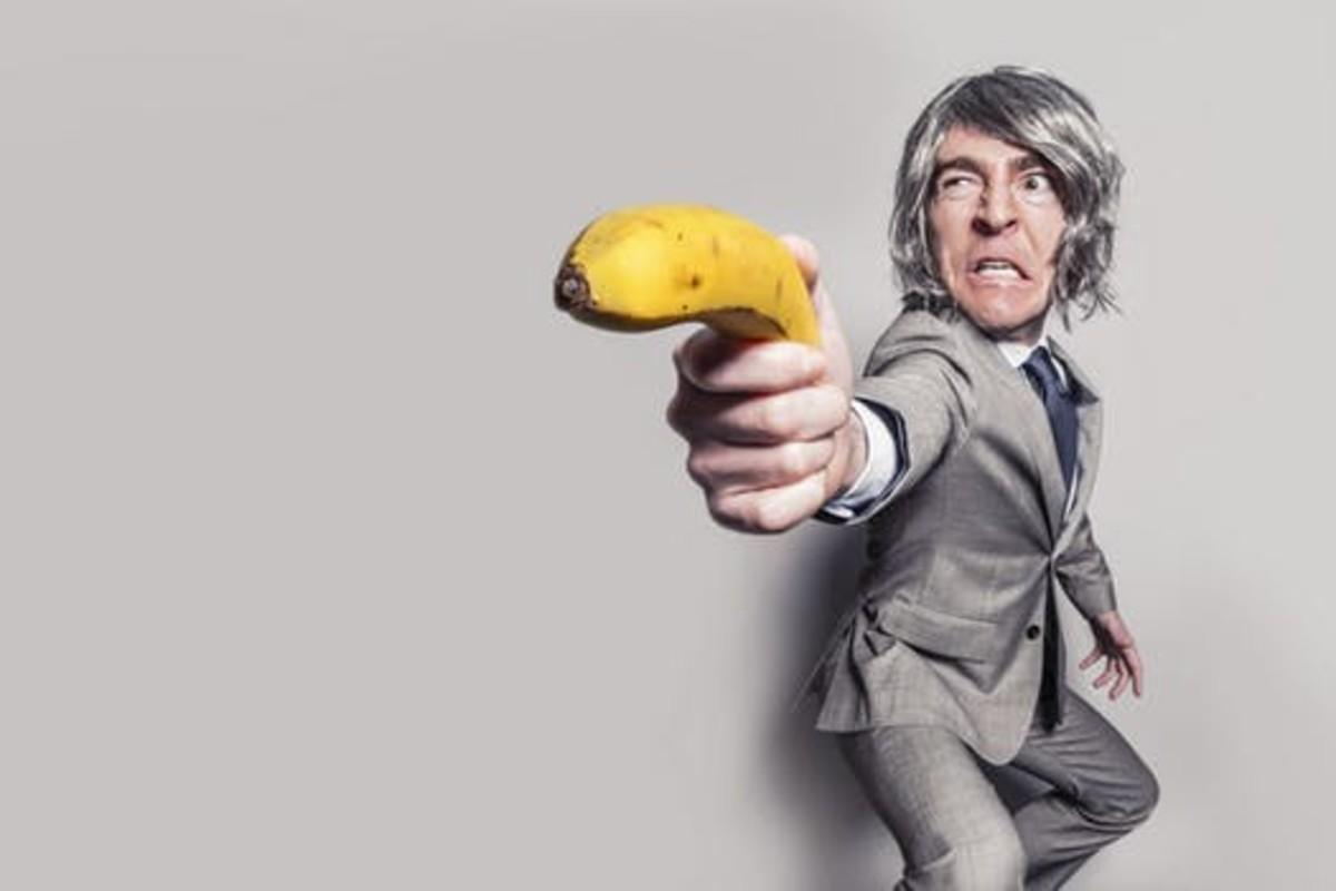 A criminal holding a banana.