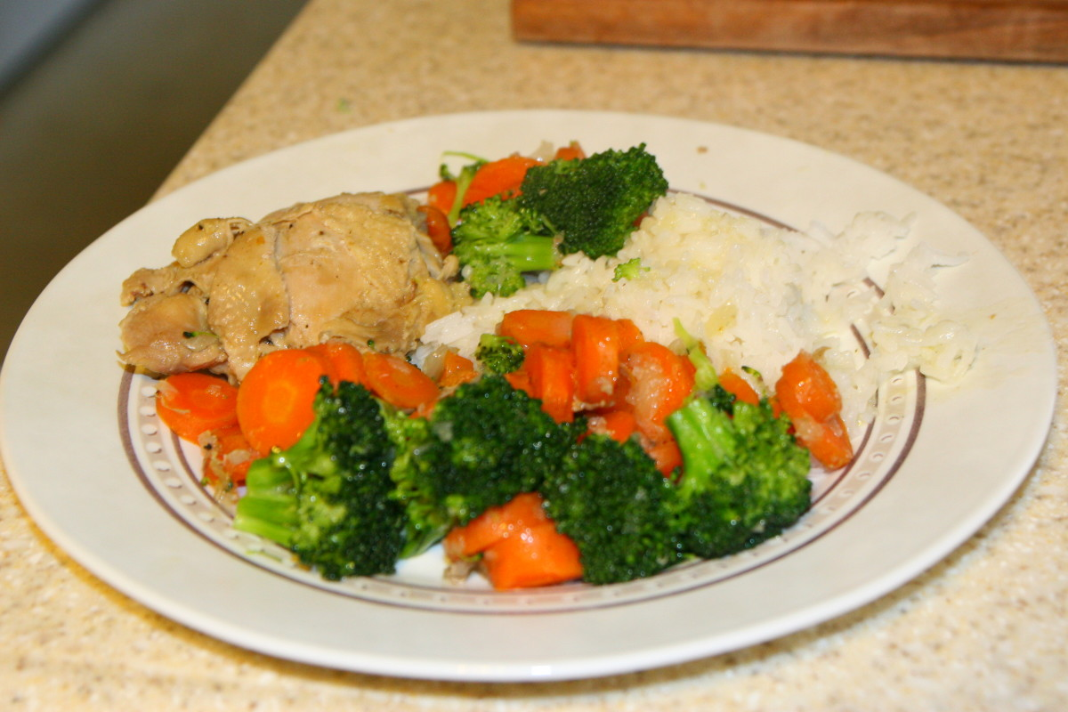 Chicken, carrots, broccoli, rice, and a thin chicken sauce make a healthy dinner.