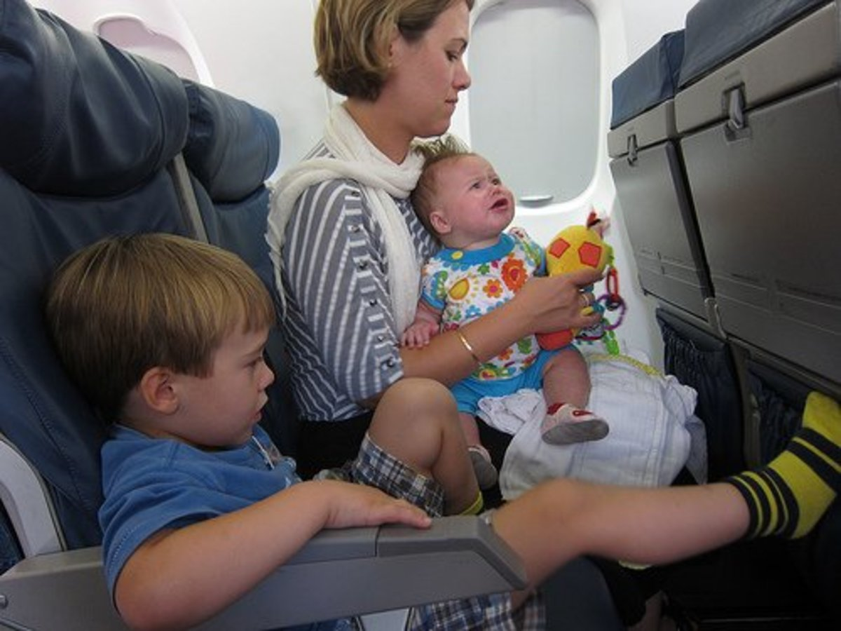 The little boy in this picture has the right idea!  He has his legs extended and elevated for the flight.  Mom is at an increased risk of clots as it looks like she recently had a baby.