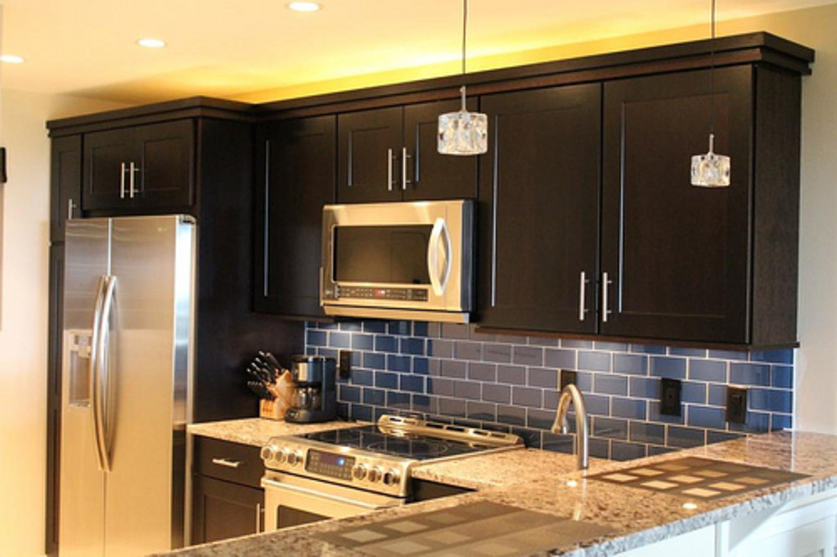 An updated backsplash,  painted cabinets, lighting and new paint will totally spruce up your old kitchen.
