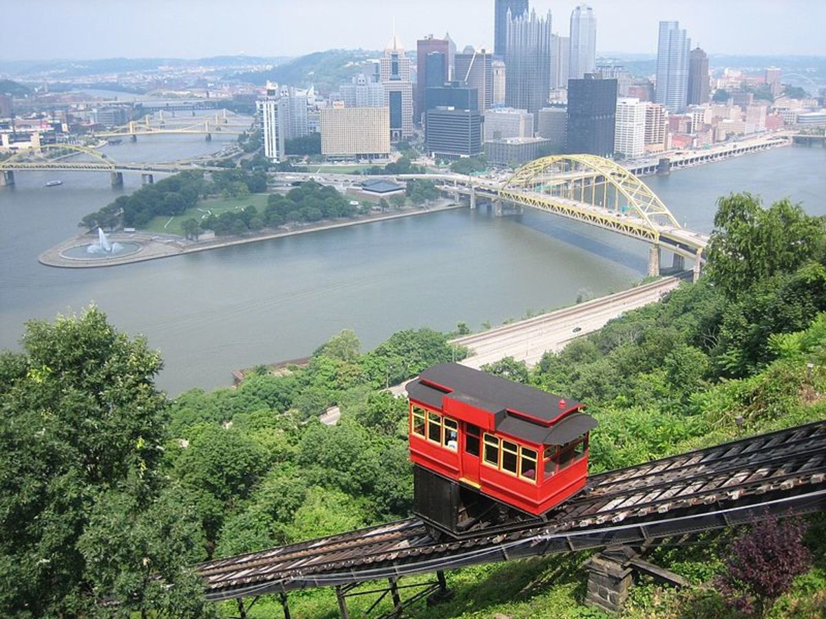 The Duquesne Incline approaches the Mount Washington Station with the downtown Pittsburgh skyline in the background.