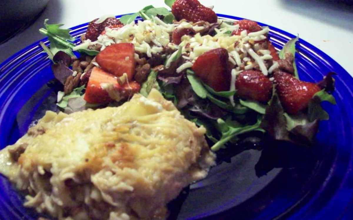 Lasagna with spring mix salad and strawberries.
