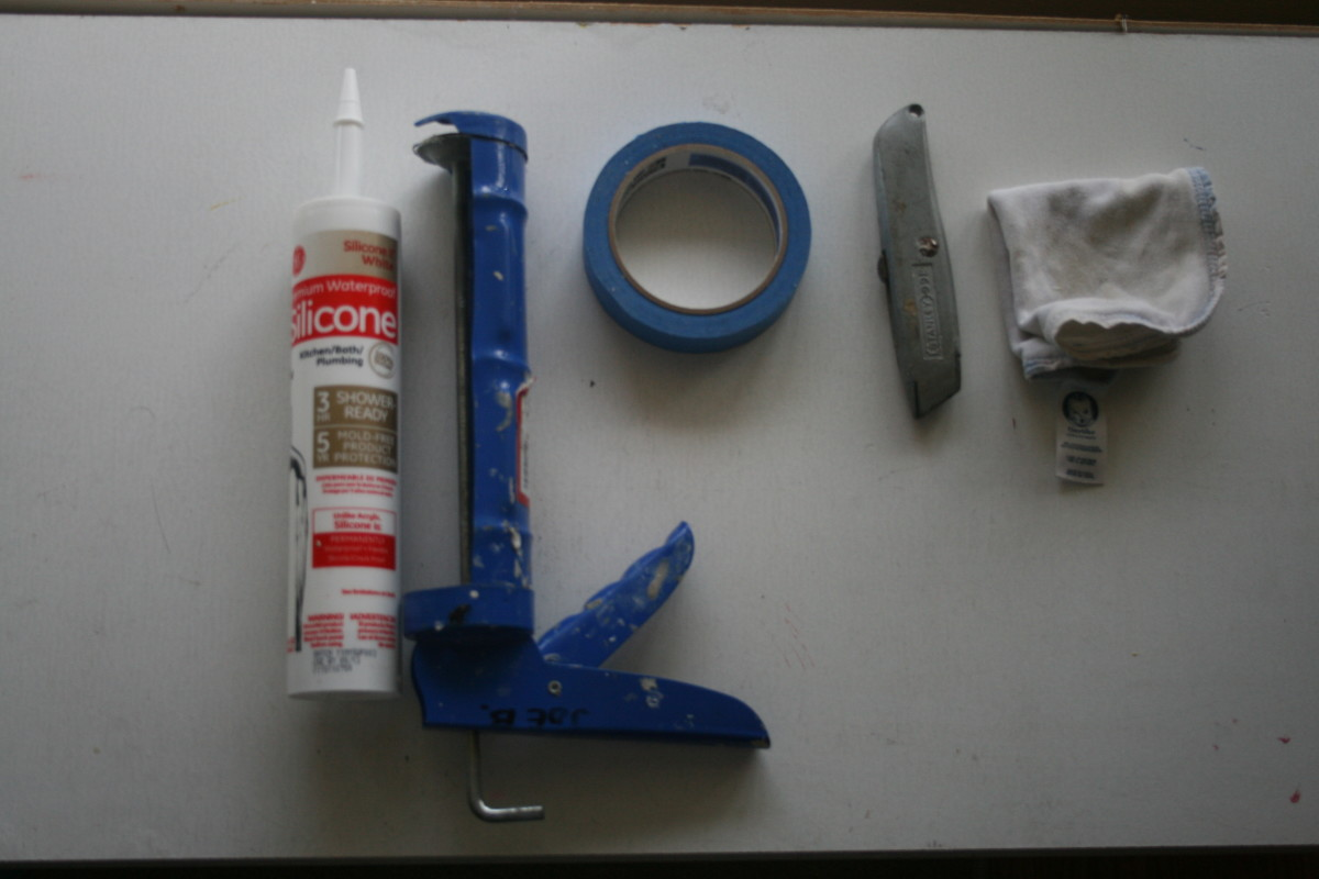 The white bath/kitchen caulk, the gun, blue painters tape, utility knife, and a washcloth. Missing is the paper towels, which come in quite handy for cleanup.
