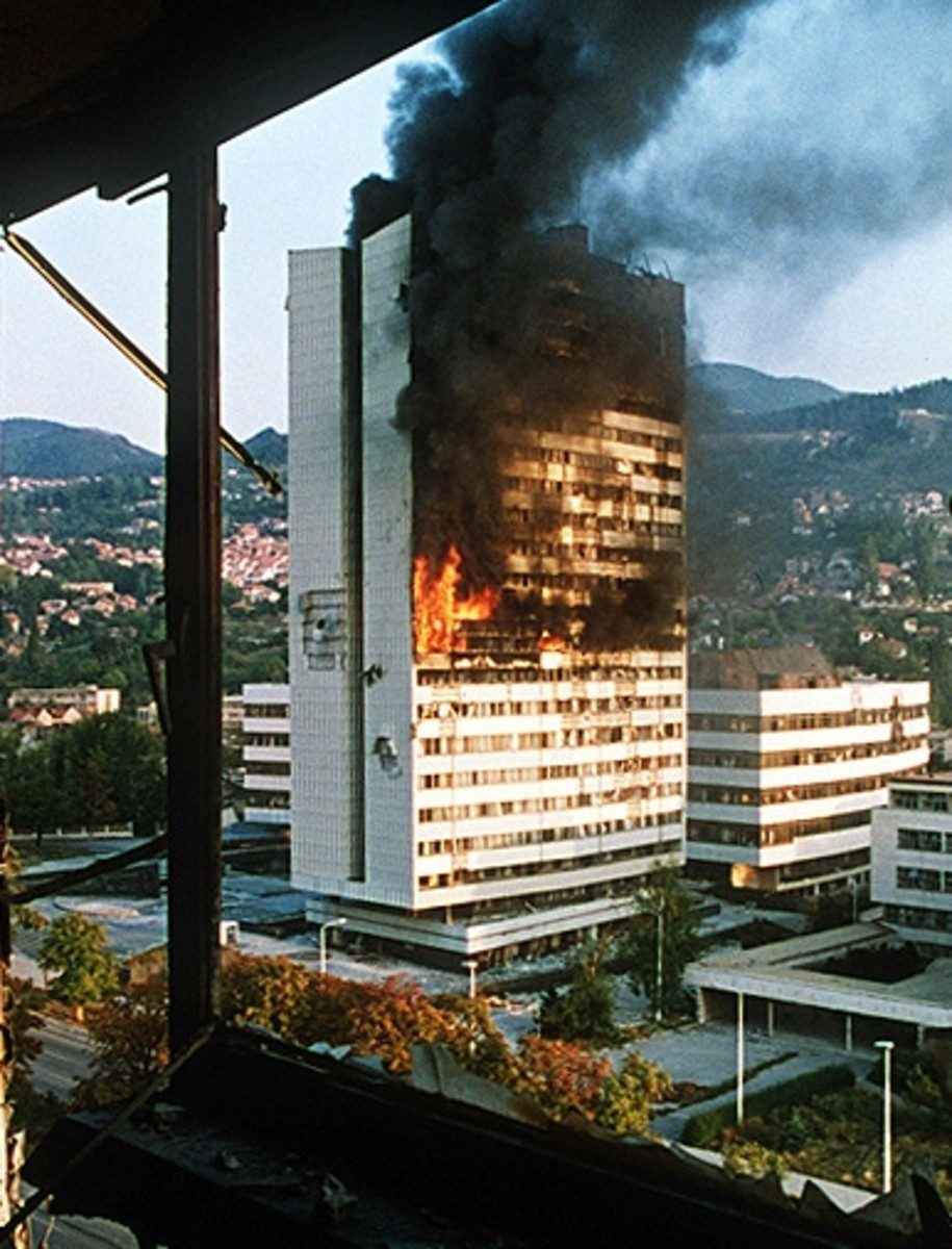 Sarajevo government building burns after being shelled by Serbian tanks (1992)