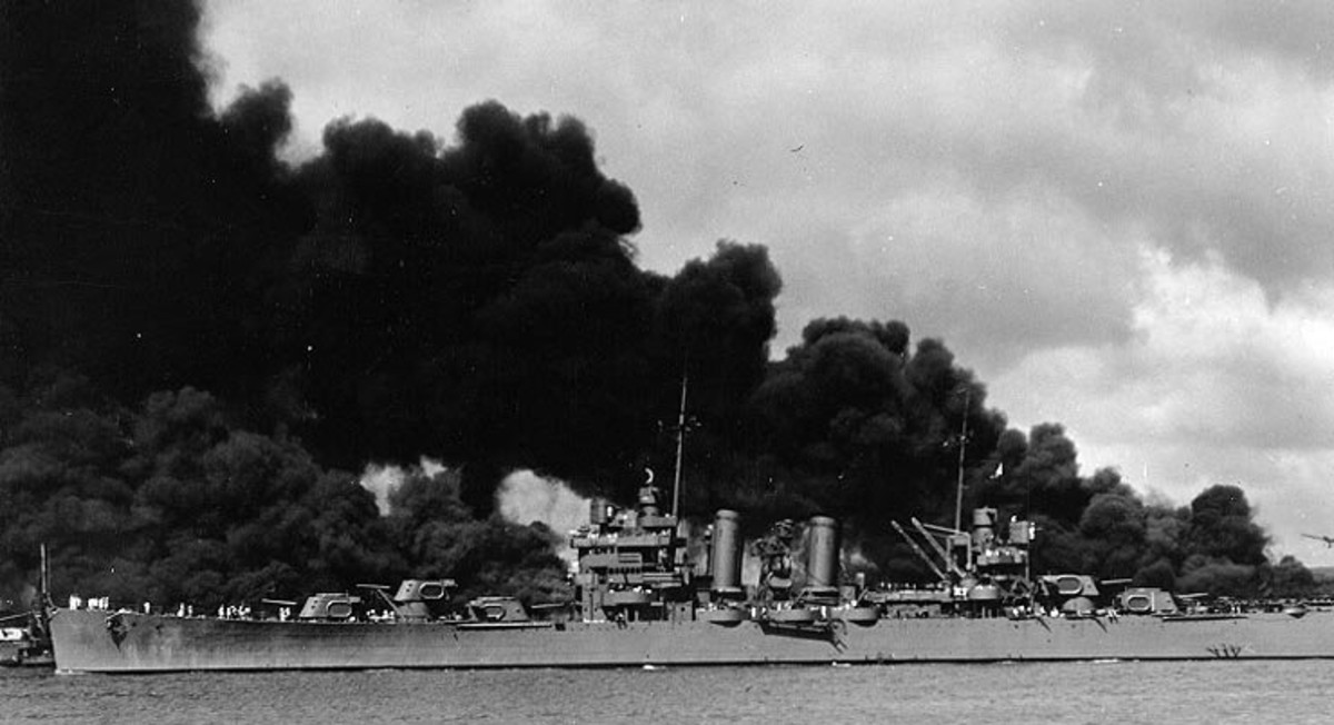 "The U.S. Navy light cruiser USS Phoenix (CL-46) steams down the channel off Ford Island's ""Battleship Row"", past the sunken and burning USS West Virginia (BB-48), at left, and USS Arizona (BB-39), at right, 7 December 1941."