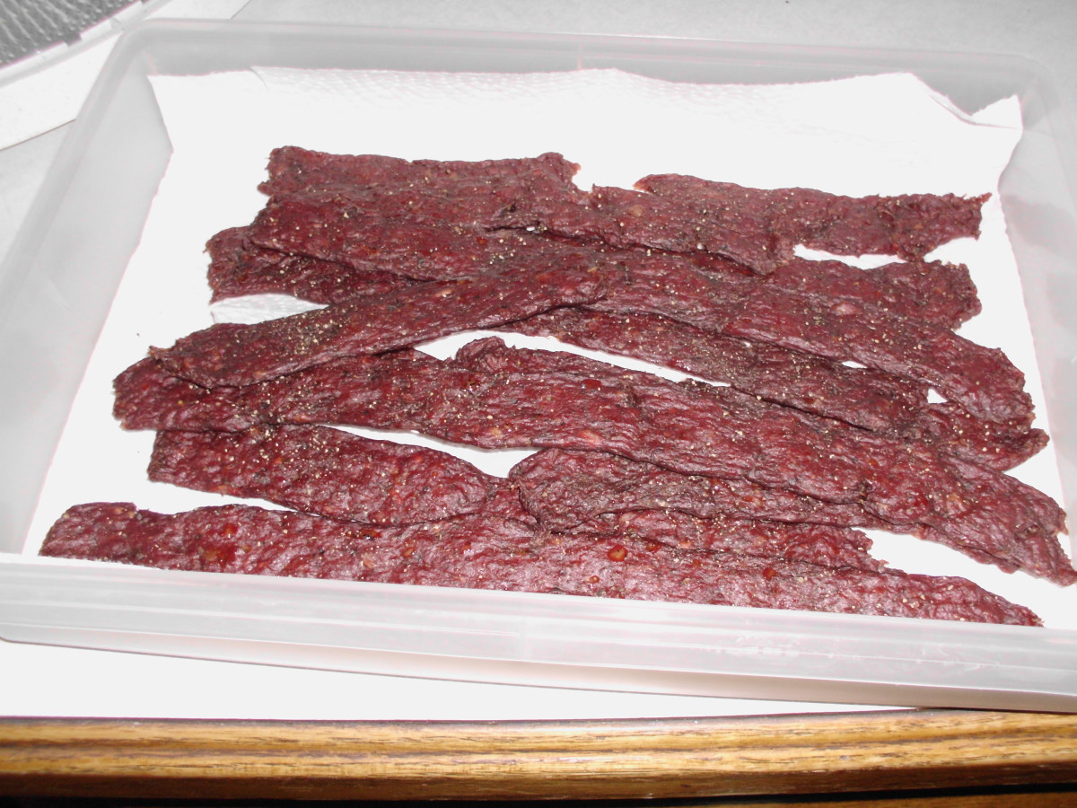 Deer jerky all done and cooling down on paper towels. You can dab the shinny grease spots off to help it dry and cool.