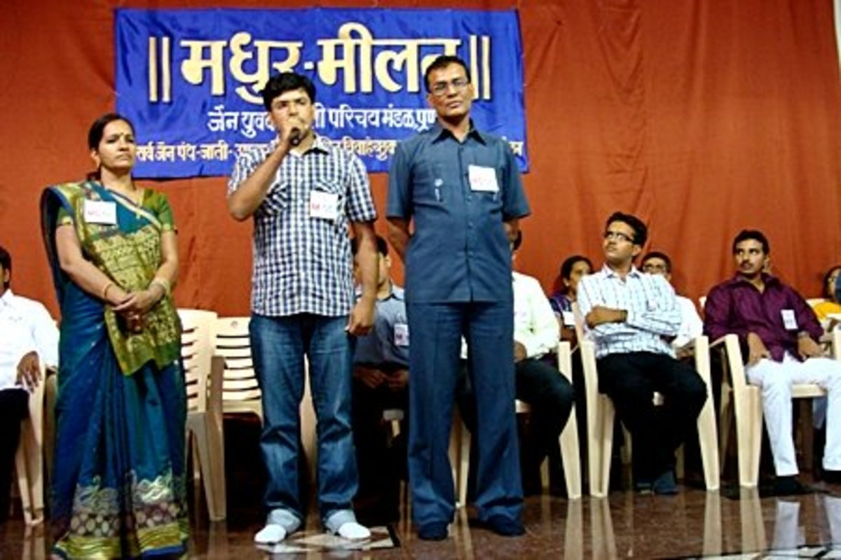A guy introducing himself in a get-together arranged by a marriage bureau. His parents stand beside him.