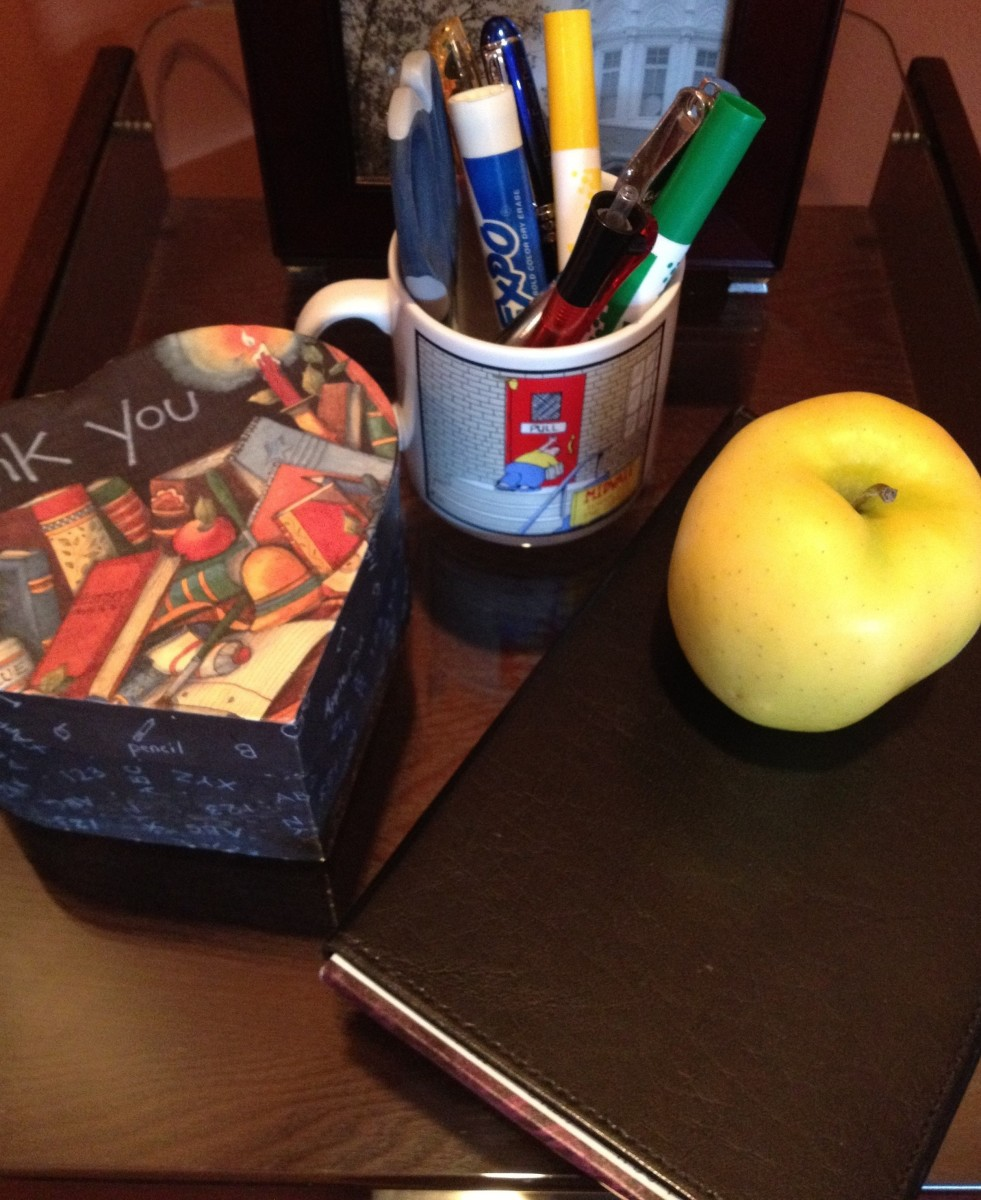 Tools of the trade: handy desk mug filled with pens, pencils, hole-punch, scissors, and markers.
