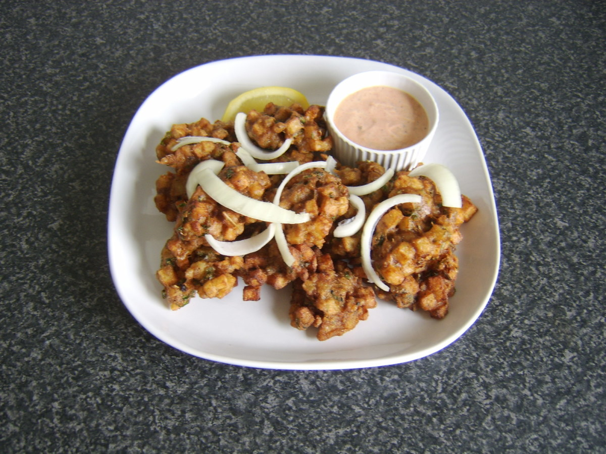Homemade vegetable pakora served with pakora sauce, onions and lemon